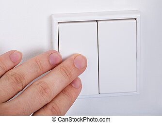Hand Presses The Light Switch On The Wall - Close-up Of Hand...