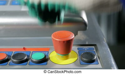 Close-up of hand pressing the red button on the desktop control panel, CNC machines for metal working. A set of buttons of different colors