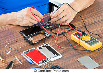 Close-up Of Hand Repairing Cellphone With Multimeter At The...