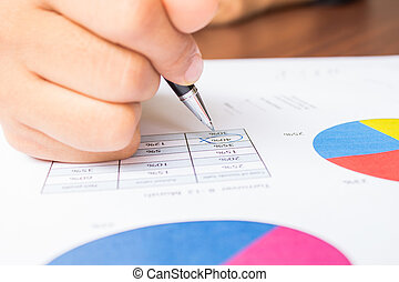Close up of hand reviewing accounting documents
