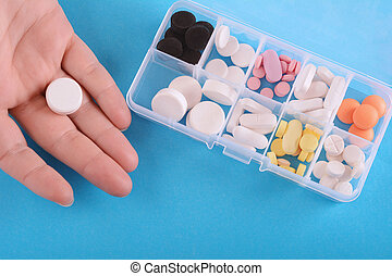 Close up of hand showing pill with medicine box