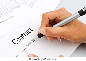 Close up of hand signing contract documents.
