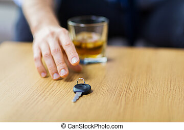 close up of hand with alcohol and car key on table
