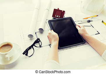 close up of hand with blueprint and tablet pc
