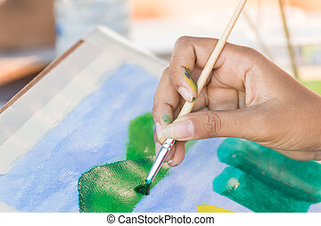 Hand with brush and paint by watercolors