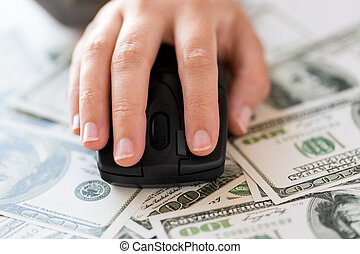close up of hand with computer mouse on money