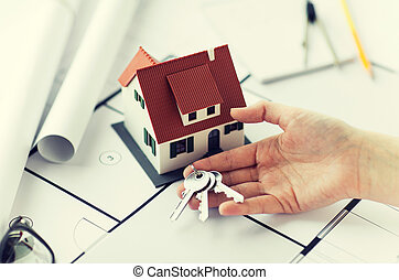 close up of hand with house keys and blueprint