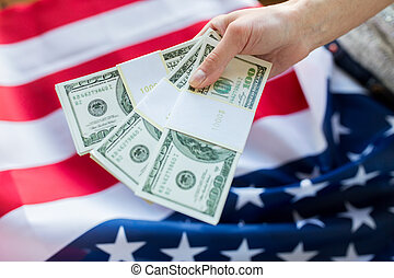 close up of hand with money over american flag