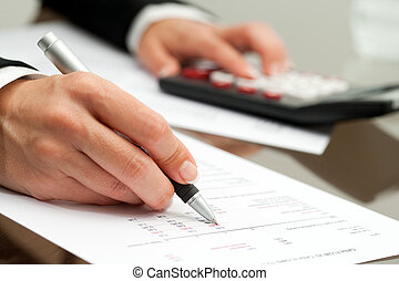 Close up of hand with pen on accounting document.