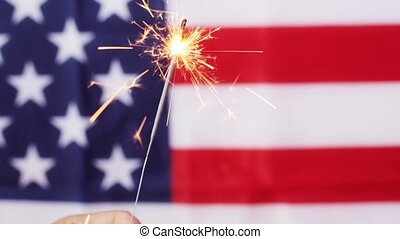 close up of hand with sparkler over american flag - american...