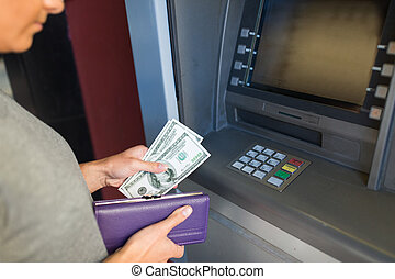 close up of hand withdrawing money at atm machine - finance,...