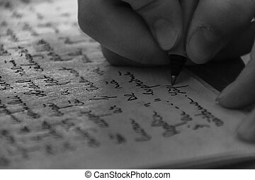 Close-Up Of Hand Writing On Paper