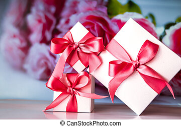 Close up of handcraft gift box with red ribbon on flower background for Christmas or New Year decoration, copy space for text