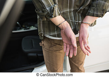 Close up of handcuffed man in a car park