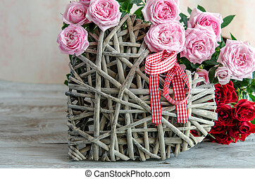 Close-up of handmade wooden heart decorated with red and pink roses