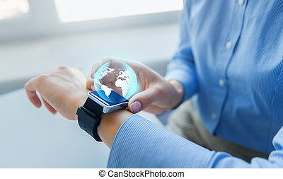 close up of hands and globe hologram on smartwatch