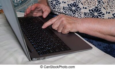 Close-up of hands and keyboard. An elderly woman is typing on a laptop