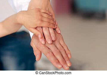 Close up of hands being put on one another