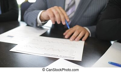 Close up of hands business investors analyzing benefits in project statistics document with rising increasing graphs in slow motion