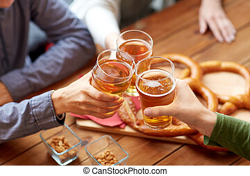 close up of hands clinking beer at bar or pub - people,...