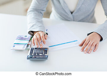 close up of hands counting money with calculator - business,...