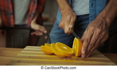 Close up of hands cutting oranges for breakfast.