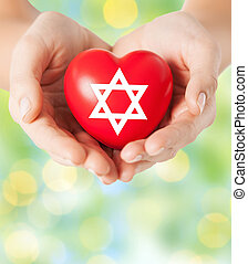 close up of hands holding heart with jewish star - religion...