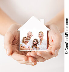 close up of hands holding house shape with family