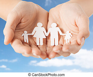 close up of hands holding paper family pictogram