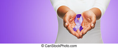 close up of hands holding purple awareness ribbon
