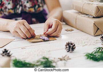 Close up of hands holding wrapping gift box and christmas card on wooden table with xmas decoration.