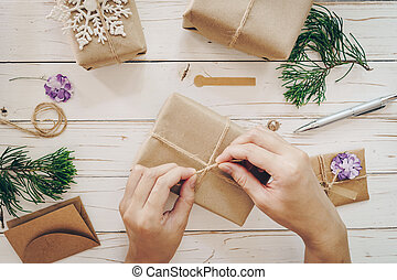 Close up of hands holding wrapping gift box on wooden table with xmas decoration.