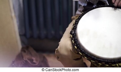 Close up of hands of a black man playing a drum. Clip....
