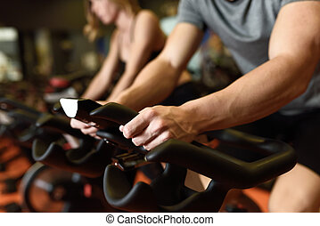 Couple in a spinning class wearing sportswear. - Close-up of...