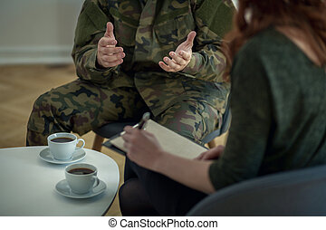 Close-up of hands of a soldier and his therapist writing on a piece of paper