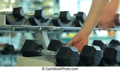 Close-up of hands of a young man who takes to perform dumbbell