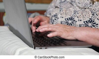 Close-up of hands of an elderly woman typing on a laptop