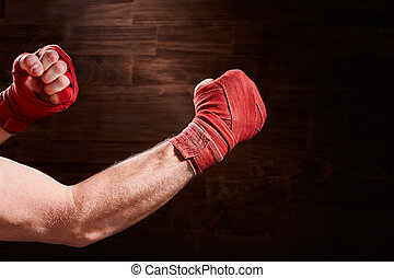 Close-up of hands of boxer with bandage ready for a fight against brown wall.
