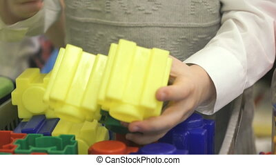 Close-up of hands of boy playing with building kit -...