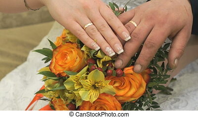 Close-up of hands of bride with bouquet and groom