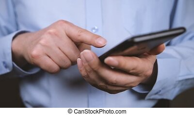 Close-up of hands of businessman using smartphone.