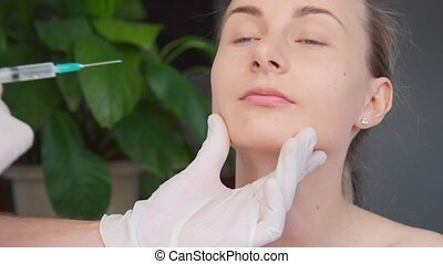 Close-up of hands of cosmetologist making botox injection to female lips. Young woman gets facial injections in salon.