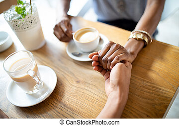 Close up of hands of couple sitting at the table and holding them together while drinking coffee