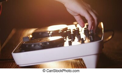 Close up of hands of DJ plays music mixing and scratching on...