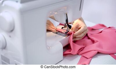 Close up of hands of needlewoman working with sewing machine in tailoring studio. Process of stitching pink cloth. Female fingers are holding material and making lines with needle and thread.