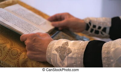 Close-up of hands of priest reading the holy bible in the...