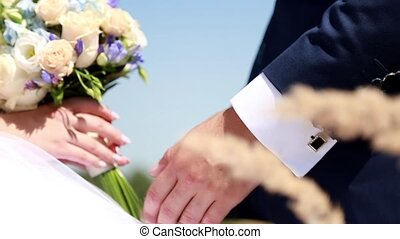 Close-up of hands of the bride and groom with bouquet