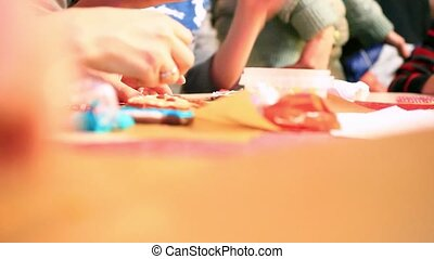 Close-up of hands painting with gingerbread cookie and...