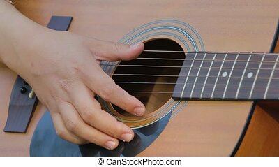 Close up of hands picking the guitar strings slow motion