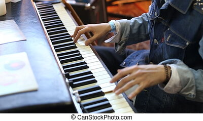 Close up of hands playing a piano.